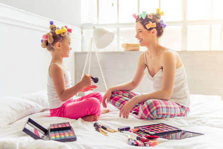 girl  care: Beautiful young mother and her daughter in pajamas and with hair curlers are doing makeup, talking and laughing, sitting on bed at home Stock Photo