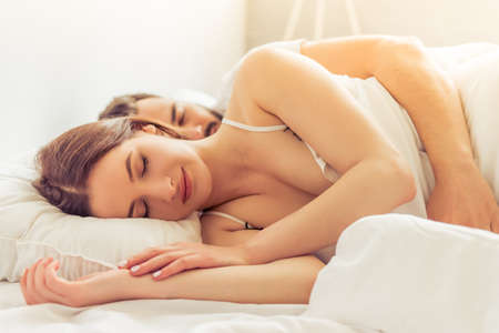 pareja durmiendo: Vista lateral de la hermosa mujer joven y su hombre abrazando mientras duerme en cama en su casa