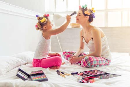 Mooie jonge moeder en haar dochter in pyjama en met haarkrullers op bed thuis. Leuk klein meisje doet haar moeder make-up