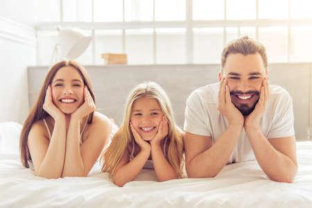 Retrato de la hermosa joven madre, padre y su hija mirando a la cámara y sonriendo mientras está acostado en la cama y apoyándose en sus manos