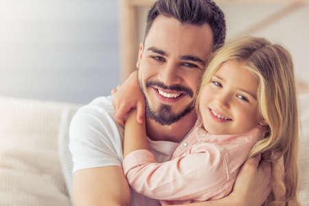 Retrato de padre guapo y su linda hija abrazando, mirando a cámara y sonriente