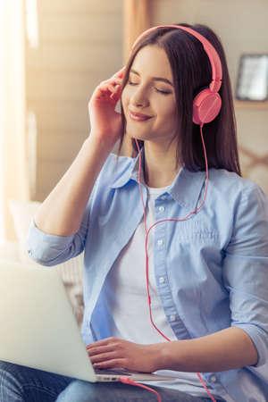 personas escuchando: Hermosa mujer joven en los auriculares está escuchando la música con un ordenador portátil y sonriendo mientras está sentado en el sofá de casa