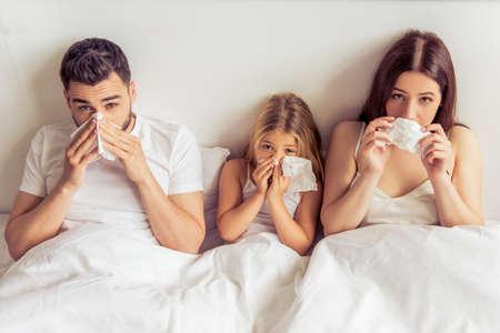 Piękne młodych rodziców i ich córki mają przeziębienia, wycierając nos i patrząc na kamery, leżąc na łóżku Zdjęcie Seryjne