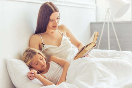 Beautiful young mother is reading a book to her little daughter, who is sleeping in bed at home Stock Photo