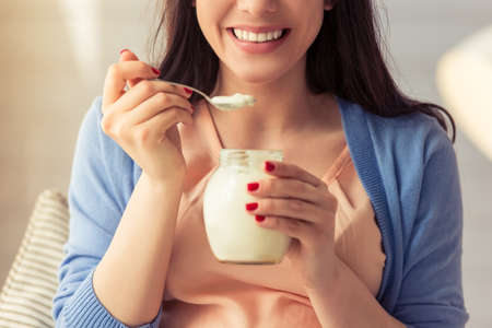 Cropped image of beautiful pregnant woman eating yogurt and smiling while sitting at home Stock Photo