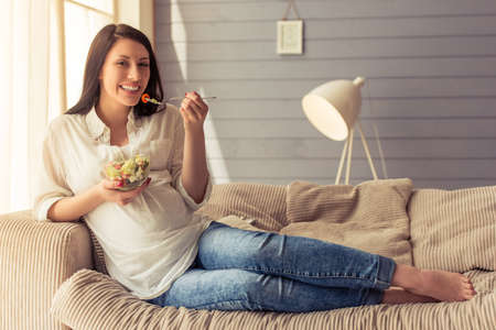 eating salad: Beautiful pregnant woman is eating salad, looking at camera and smiling while sitting on couch at home