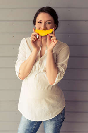 Beautiful pregnant woman is eating fruit, looking at camera and smiling, standing against gray wall Stock Photo