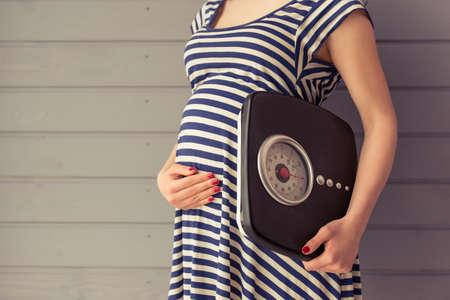美しい妊婦腹、灰色の壁に立っている体重計と維持する 1 つの手を保持してのトリミングされた画像 写真素材
