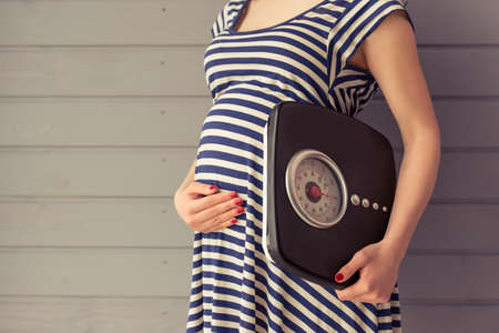 Cropped image of beautiful pregnant woman holding weigh scales and keeping one hand on a belly, standing against gray wall Reklamní fotografie - 58102602