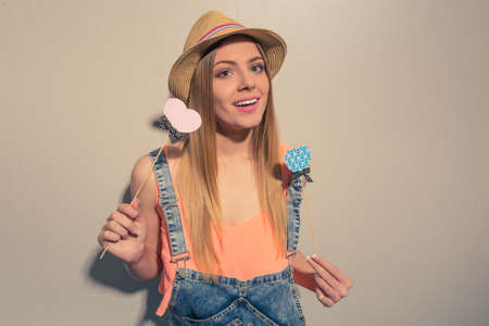 wood stick: Attractive girl in summer clothes is posing with paper hearts on wood stick, looking at camera and smiling, against gray background Stock Photo