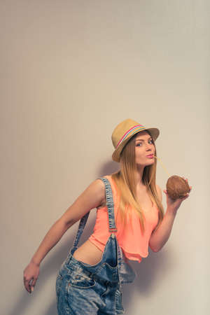 studio happy overall: Attractive girl in summer clothes and hat is drinking a coconut milk, looking at camera and smiling, against gray background