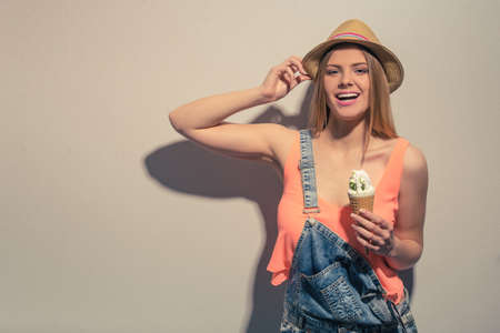 studio happy overall: Attractive girl in summer clothes is holding an ice cream, looking at camera and smiling, against gray background Stock Photo