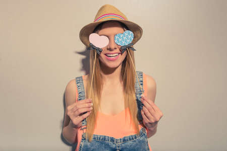 covering eyes: Attractive girl in summer clothes is covering eyes with paper hearts on wood stick and smiling, against gray background