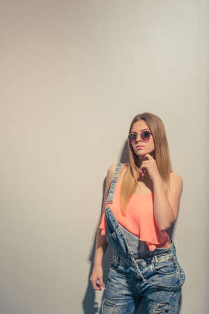 studio happy overall: Attractive pensive girl in summer clothes and sun glasses is looking at camera and posing, against gray background