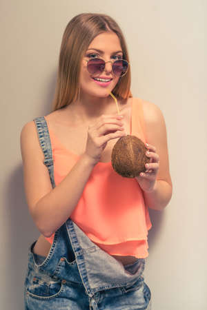 studio happy overall: Attractive girl in summer clothes and sun glasses is drinking a coconut milk, looking at camera and smiling, against gray background