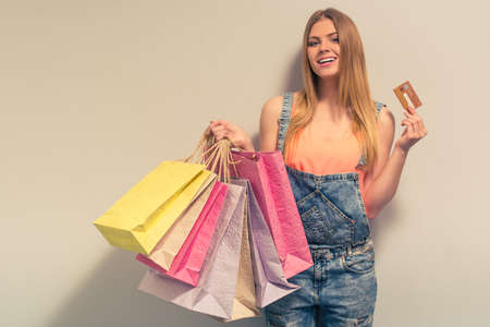 ropa de verano: Attractive girl in summer clothes is holding shopping bags and a credit card, looking at camera and smiling, against gray background Foto de archivo