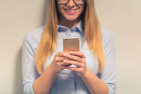 probation: Cropped image of attractive girl in classic clothes and eyeglasses using a smartphone and smiling, against gray background