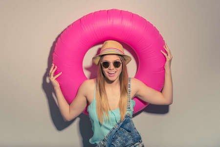 studio happy overall: Attractive girl in summer clothes and sun glasses is holding a swim ring, looking at camera and smiling, against gray background Stock Photo