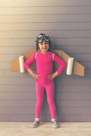 akimbo: Cute little girl dressed like a pilot with toy wings is smiling and looking at camera, standing akimbo against gray wall Stock Photo