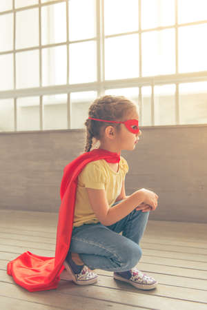 girl squatting: Side view of cute little girl dressed like superhero playing at home, squatting against windows