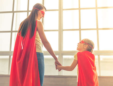 Back view of mother and her little daughter dressed like superheroes holding hands, looking at each other and smiling, standing against windows Stock Photo