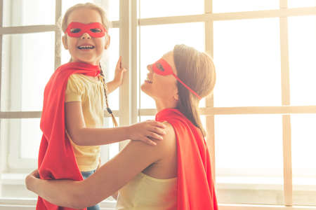 Beautiful mother and her little daughter dressed like superheroes are smiling while playing at home Stock Photo