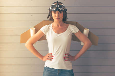 akimbo: Beautiful young woman dressed like a pilot with toy wings is smiling and looking upward, standing akimbo against gray wall