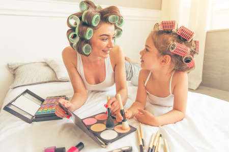 powder room: Beautiful young mother and her cute daughter with hair curlers on heads are doing makeup, looking at each other and smiling, sitting on bed