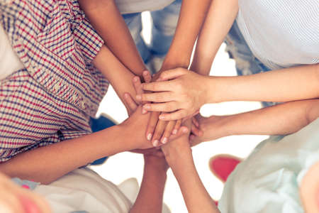 Top view of group of teenage boys and girls keeping hands together, cropped Stok Fotoğraf - 58684616