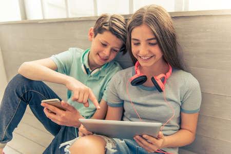Adolescente menino e menina com fones de ouvido estão usando gadgets, conversando e sorrindo enquanto está sentado no chão