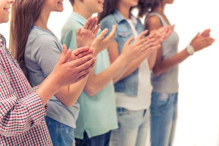 Bijgesneden afbeelding van de groep van jongens en meisjes handgeklap, staan in een rij, geïsoleerd op wit Stockfoto