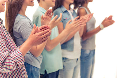 Cropped image of group of teenage boys and girls clapping hands, standing in a row, isolated on white