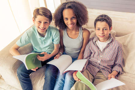 american stories: High angle view of three teenagers, boys and a girl, are reading, looking at camera and smiling while sitting on the couch at home Stock Photo