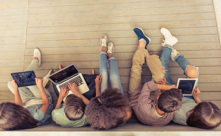 beautiful boy: Top view of group of teenage boys and girls using gadgets while sitting in row on wooden floor Stock Photo