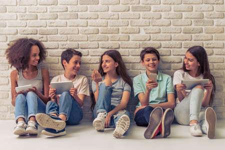 Grupo de adolescentes meninos e meninas está usando gadgets, conversando e sorrindo, sentado contra a parede de tijolos brancos