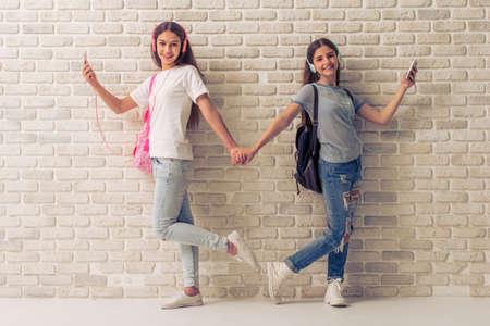 Dos adolescentes en los auriculares se escucha música en los teléfonos inteligentes, la mano y sonriendo, de pie contra la pared de ladrillo blanco