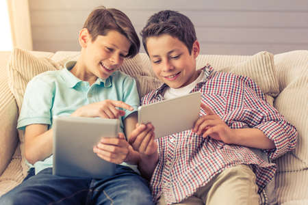 Two attractive teenage boys are using tablets, talking and smiling while sitting on the couch at home