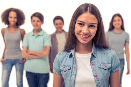 Attractive teenage girl regarde la caméra et souriant, isolé sur blanc, d'autres adolescents en arrière-plan Banque d'images