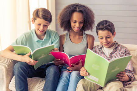 american stories: Three teenagers are reading and smiling while sitting on the couch at home. Attractive afro american girl is sitting between boys Stock Photo