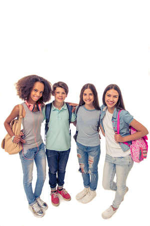 standing together: Full length portrait of group of teenage boys and girls with school backpacks looking at camera and smiling, standing, isolated on white Stock Photo