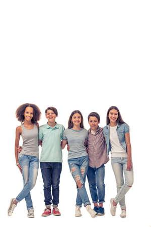 Retrato de cuerpo entero de un grupo de adolescentes y niñas abrazos, mirando la cámara y la sonrisa, se colocan en fila, aislado en blanco Foto de archivo
