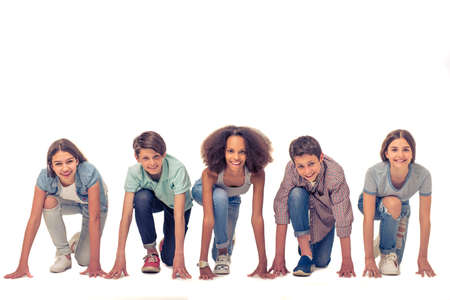 standing together: Group of teenage boys and girls is looking at camera and smiling while standing on starting line, isolated on white