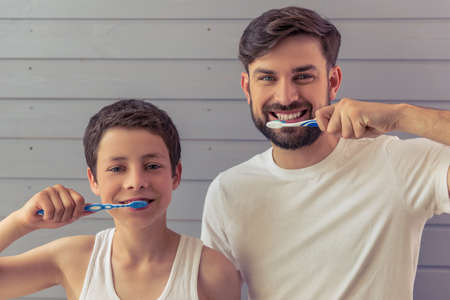 Handsome young father and his teenage son are brushing teeth, looking at camera and smiling, against gray wall Фото со стока