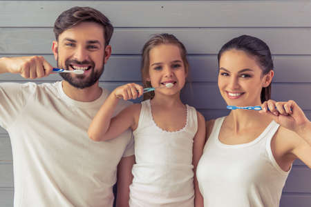 Beautiful young parents and their cute little daughter are looking at camera and smiling while brushing teeth, against gray wall Stock Photo
