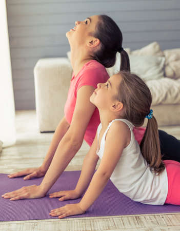 Beautiful young mother and her cute little daughter are smiling while stretching on yoga mat at home