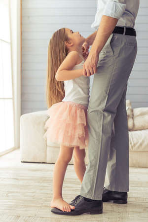 suit skirt: Cropped image of young father and his cute little daughter dancing at home. Girl is standing on her fathers feet, looking at her dad and smiling