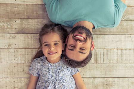 Vista superior de apuesto joven padre y su pequeña hija linda mirando a la cámara y sonriendo, acostado en el piso de madera