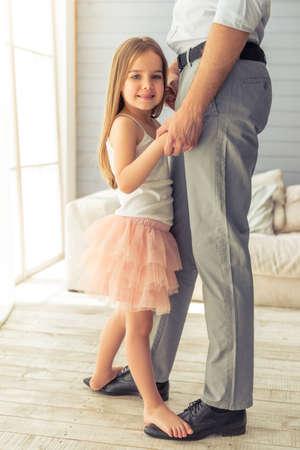 Bebouwd beeld van jonge vader en zijn schattige dochtertje dansen thuis. Het meisje bevindt zich op de voeten van haar vader, kijkend naar de camera en lacht