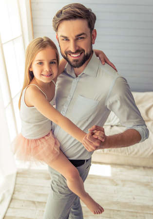 dancefloor: Handsome young father and his cute little daughter are dancing at home, looking at camera and smiling