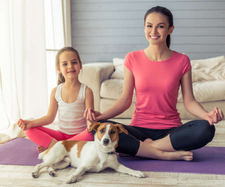 mum and daughter: Beautiful young mother and her cute little daughter are looking at camera and smiling while sitting in lotus pose with their dog on yoga mat at home